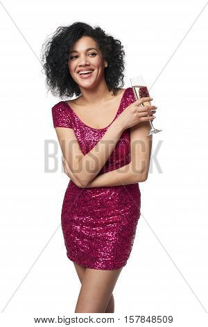 Party, drinks, holidays and celebration concept. Happy playful laughing mixed race woman in sequined dress with glass of champagne, looking to the side at blank copy space