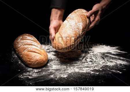 Crunchy and fresh. Close up of chef mans hands holding a loaf of bread while demonstrating it after baking.