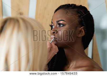 beautiful african model preparing to shooting. Make up artist doing make up on her lips. Black woman with white lips