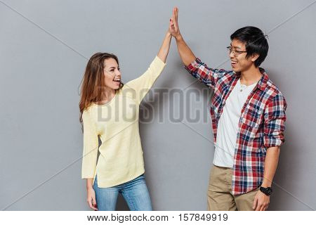 Portrait of a beautiful young couple standing and giving high five isolated on the gray background