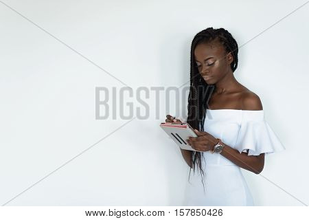 Model with black skin is standing in front of a white wall and chatting in internet using her tablet. Girl is wearing white dress with bare shoulders.