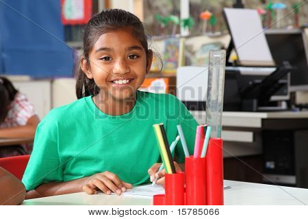 Schoolgirl smile at desk in class