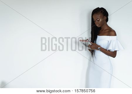 Sexy pretty photo model with black skin is standing in front of a white wall and chatting in internet using her tablet. Girl is wearing long white dress with bare shoulders and watch on her hand