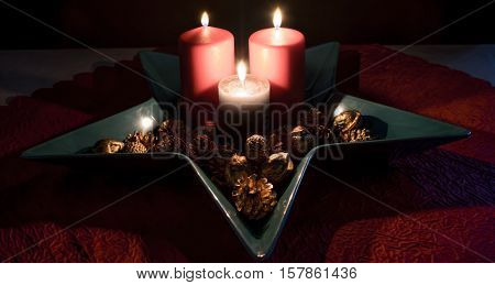 3 lighted candles in a star-shaped Bowl decorated with Golden pinecones and walnuts on a red tablecloth.