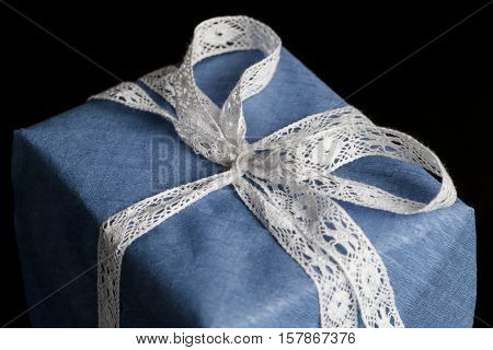 Closeup on white lace ribbon bow tied on wrapped in blue textured paper gift on black background
