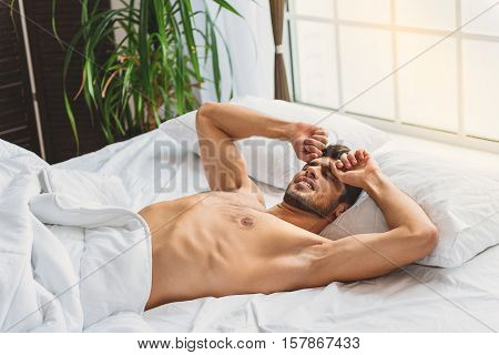Serene young man is waking up in morning. He is stretching arms and touching his face