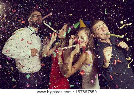 Two beautiful young couples having fun at New Year's party wearing party hats dancing and blowing party whistles. Focus on the couple on the right
