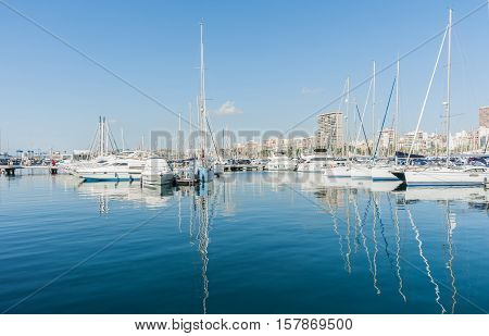 Alicante, Spain - September 9, 2016;  Marina and luxury boats yacht masts reflected in calm turquoise water with city skyline behind Alicante Spain