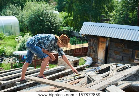 A young man grabs a tool lying on the roof of unfinished barn in the village