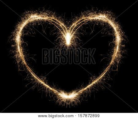 New year party burning sparkler heart shape on black background. Glowing holiday sparkling hand fireworks, love symbol shining fire flame. Christmas light.