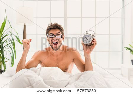 I oversleep. Young man is sitting on bed and holding alarm-clock. He is screaming with shock