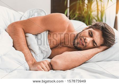 Bad dream. Man is lying in bed and sleeping. He frowning with closed eyes