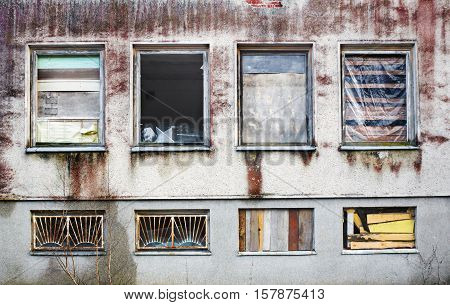 Windows boarded up by wooden panels in an old house with beat all glass