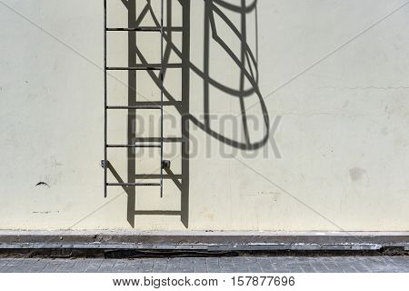 Iron roof access ladder against dirty wall