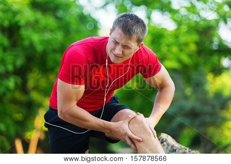 Muscle injury. Man with sprain thigh muscles. Athlete in sports shorts clutching his thigh muscles after pulling or straining them while jogging on the beach