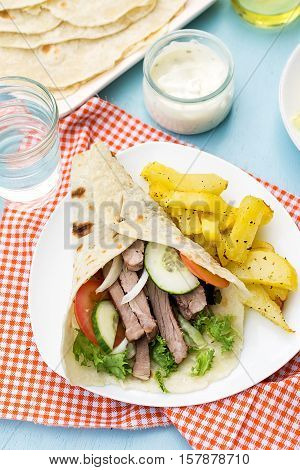 Greek gyros with pork vegetables potatoes and homemade pita bread