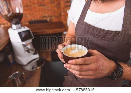 Close up of barista arms holding cup of latte while standing in coffeehouse