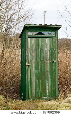 Green outdoor toilet near the field unsanitary concept village