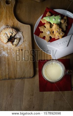 Overhead shot on wooden table of biscuits (cookies) milk and mince pies left out on Christmas Eve for Santa with list in envelope.