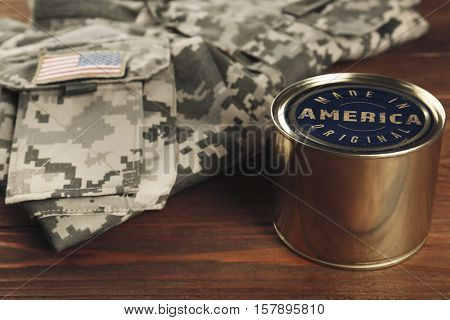 Tin of combat ration with text MADE IN AMERICA ORIGINAL and military uniform on wooden background, closeup. Manufacturing quality concept.