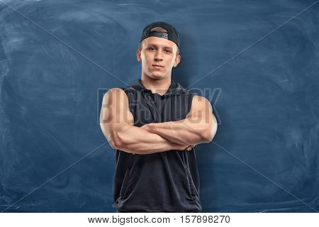 A muscular young man in his sportswear standing with his arms folded on the dark blue background. Sport and healthy lifestyle. Keep fit. Athletic body.
