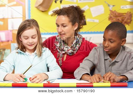 Schoolgirl And Schoolboy Studying In Classroom With Teacher