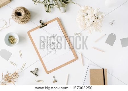 Flat lay top view office table desk. feminine desk workspace with clipboard and inspirational quote twine pencils floral bouquet craft diary and clips on white background.