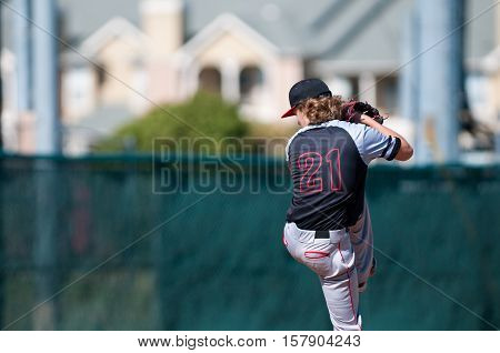 American teenage high school pitcher on the mound during a game.
