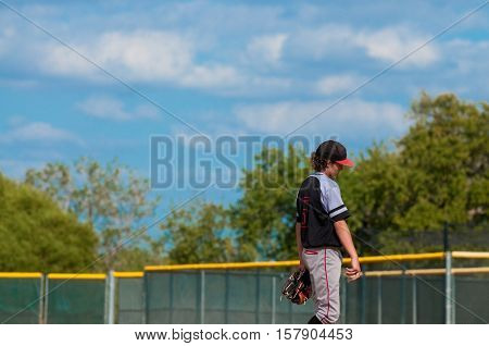 Baseball pitcher in black and grey jersey looking sad during a game.