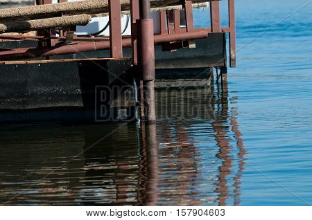 The corner of a metal boat dock on the tranquil lake.