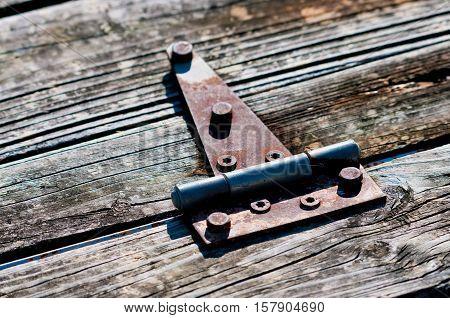 Old rusted metal hindge on weathered wood on a bridge.