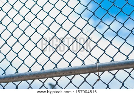 Baseball chain link fence with blue sky and white clouds in background.