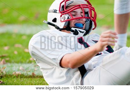 Young american football player on ground close up after getting tackled.