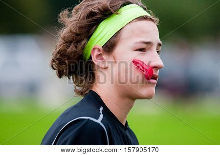 Young athlete playing 7 on 7 football with gloves and headband with mouthpiece in mouth.