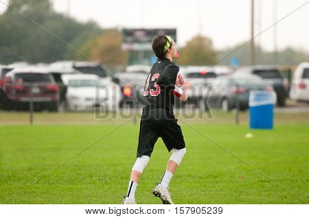 Young athlete playing 7 on 7 football with gloves and headband.