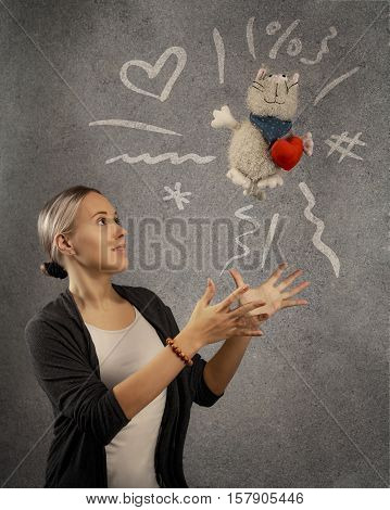 Young beautiful blond woman tosses plush toy cat with plush heart. Doodle sketch is drawn on grey texture background. Holiday gift concept with copy space