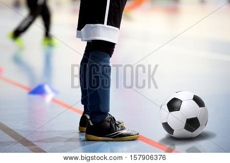 Football futsal training session. Futsal player with soccer ball. Indoor soccer young player with a soccer ball in a sports hall. Sport background