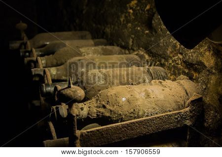 Dusty bottles of wine resting in a cave since many years.
