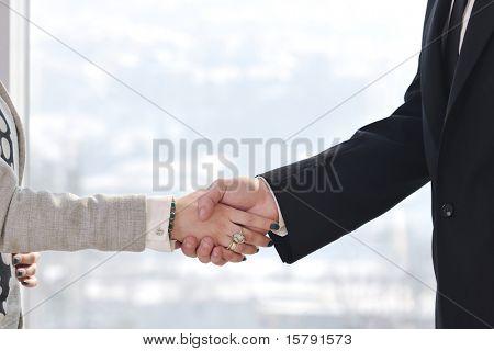saludo de hombre y mujer de negocios en el éxito de la reunión en sala de conferencias de la oficina brillante interior