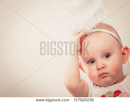 Christmas holiday concept. Little baby wearing christmassy clothes with aureole on head.