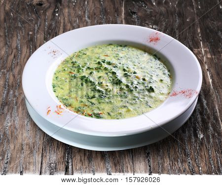 Broccoli cream-soup. Plate on the wooden table.