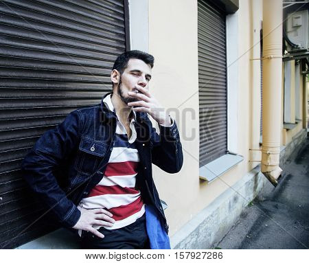 middle age man smoking cigarette on bacyjard, stylish tough guy, lifestyle people concept close up