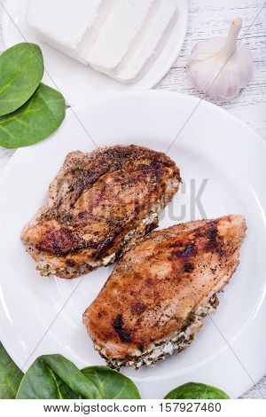 Spinach and feta stuffed chicken breast on the wooden background.