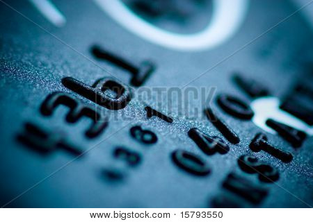 Teal credit card digits close-up. Shallow DOF.