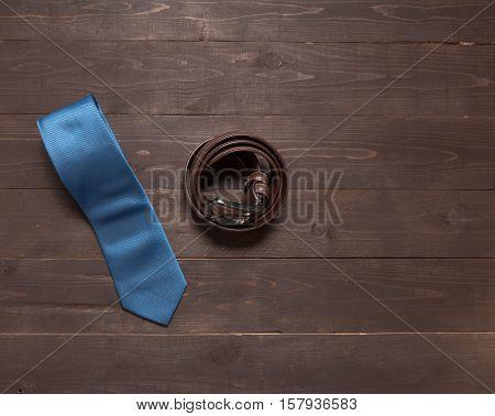 Elegant Set: Blue Tie, Brown Leather Belt, On The Wooden Background