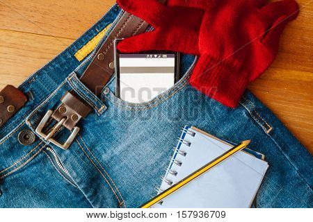 Jeans Trousers With Leather Belt And Smartphone In Pocket, Gloves And Notepad On Wooden Board