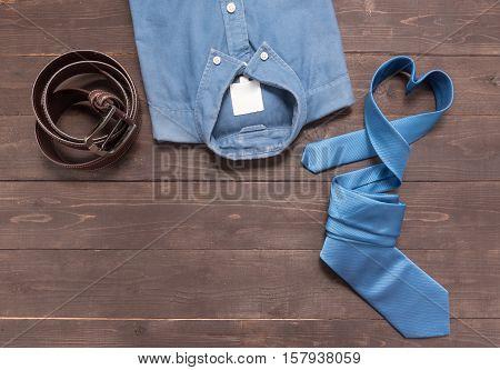 Elegant Set: Brown Leather Belt, Blue Shirt And Blue Necktie On The Wooden Background