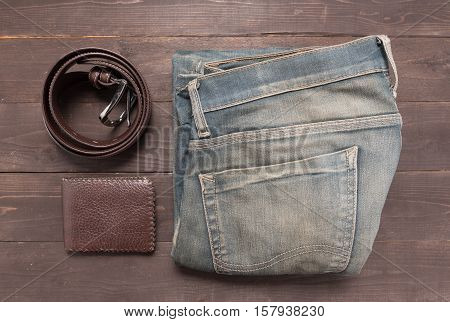 Elegant Set: Brown Wallet, Jeans And Brown Leather Belt, On The Wooden Background