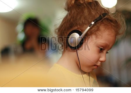 Little girl listening fairytale in headphones. Shallow DOF.