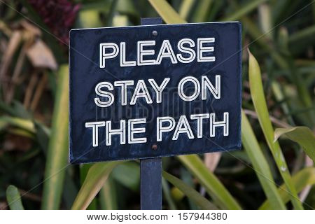 Please stay on path sign in garden with green foliage backdrop.